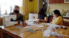 Muchachas romanís de una asociación cívica cosen máscaras