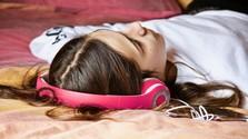 dievča so slúchadlami na posteli