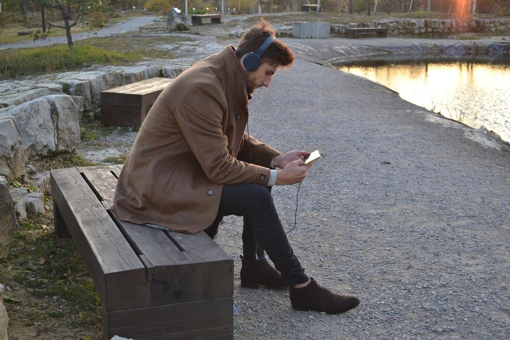 muž počúva hudbu v parku