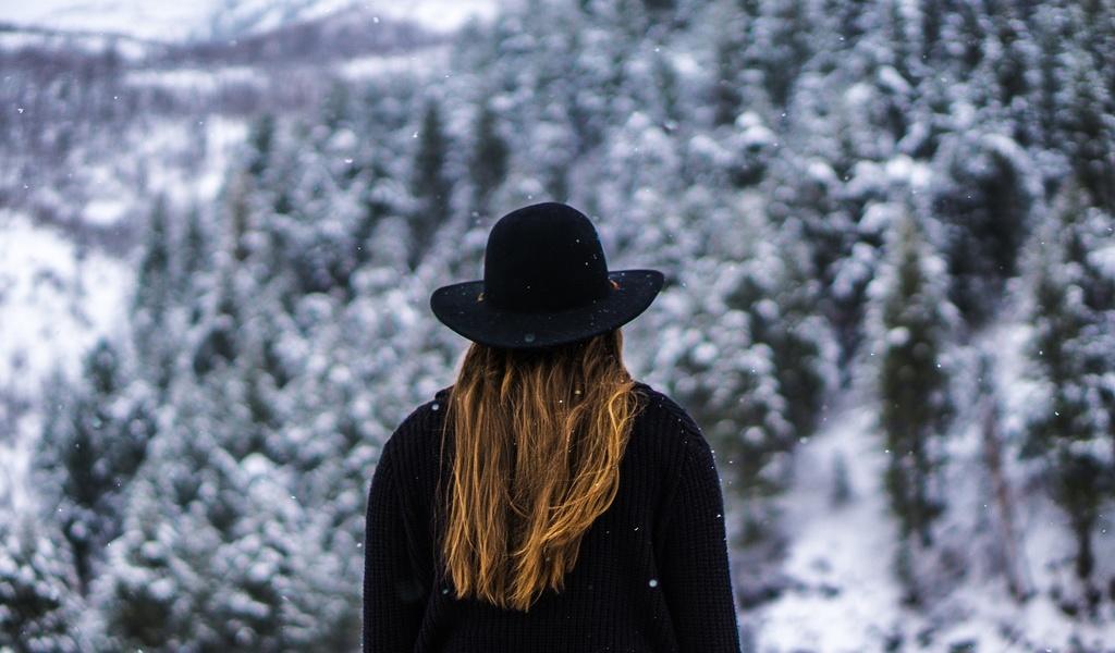 žena v klobúku v zasneženom lese